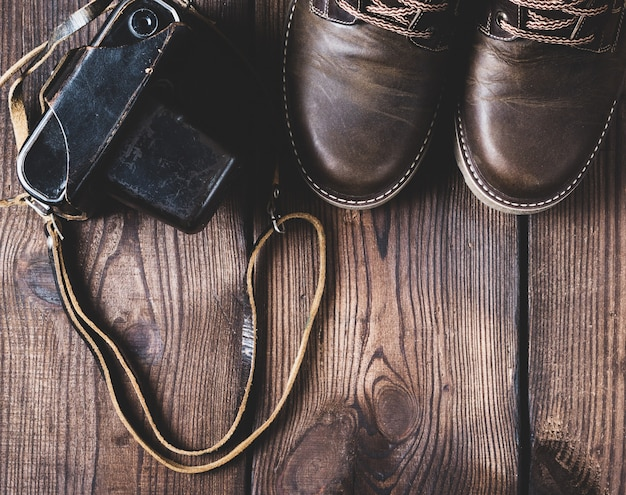 Leather brown shoes and an old vintage camera Premium Photo
