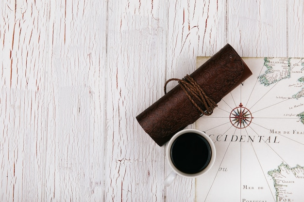 Leather case and cup of coffee stand on white travel map Free Photo