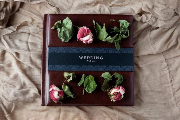 革で覆われた結婚式の写真アルバムのトップビューにバラの花の装飾 Premium写真