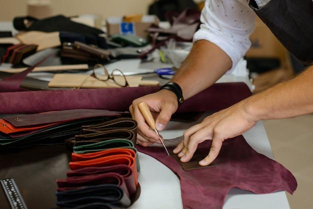 Leather handbag craftsman at work in a workshop Premium Photo