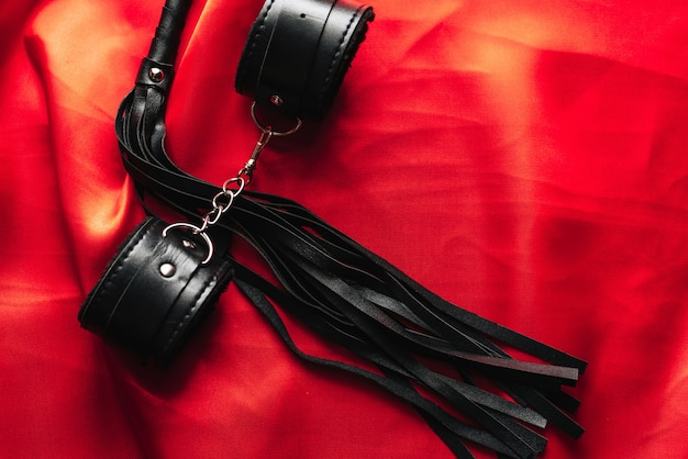 Leather handcuffs and black whip for sex games in bdsm sex Premium Photo