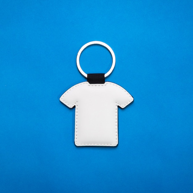 Leather key ring in shirt shape on blue paper background Premium Photo