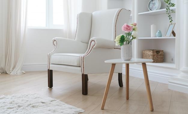 白い革張りのアームチェアと明るい部屋で花瓶とモダンな木製のテーブル Premium写真