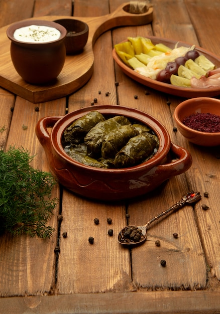 Leaves dolma in pot with side pickles Free Photo