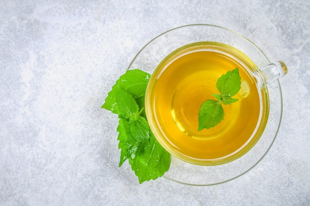 Leaves of fresh green nettle and a clear glass cup of herbal nettle tea on a gray concrete table. Premium Photo