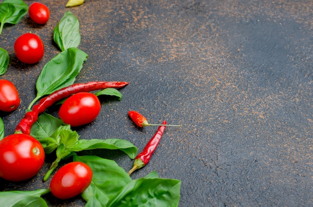 Leaves green basil, cherry tomatoes and pepper spice Premium Photo
