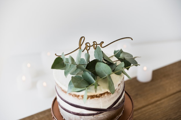 Leaves and love text on decorative round cake over the wooden table Free Photo