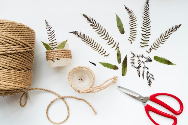 Leaves; scissor; jute string and wrapped candles on white background Free Photo