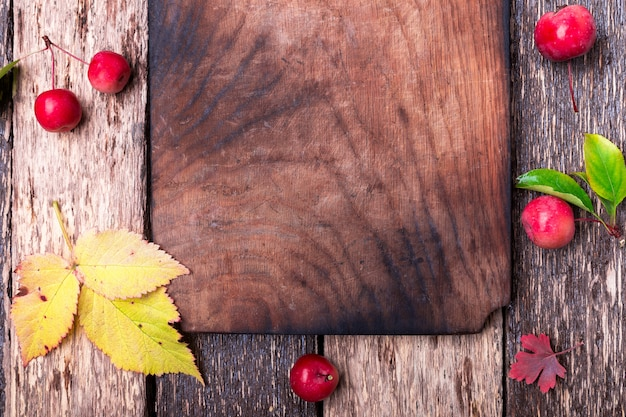 Leaves and small apple around empty cutting board Premium Photo