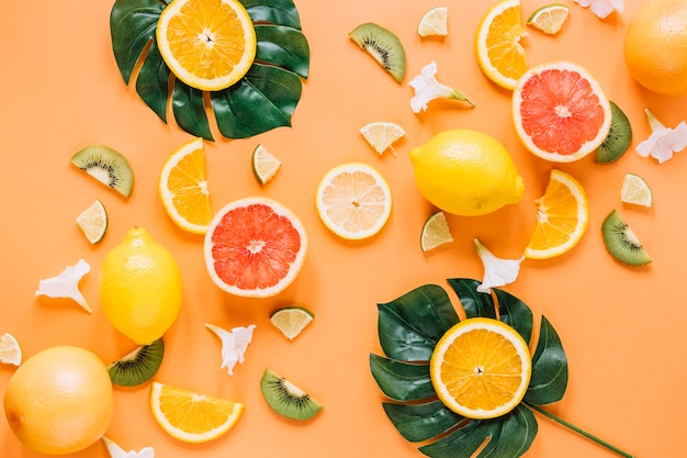 Leaves with oranges near fruits and flowers Free Photo