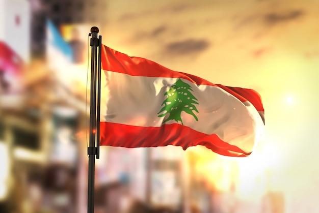 Lebanon flag against city blurred background at sunrise backlight Premium Photo