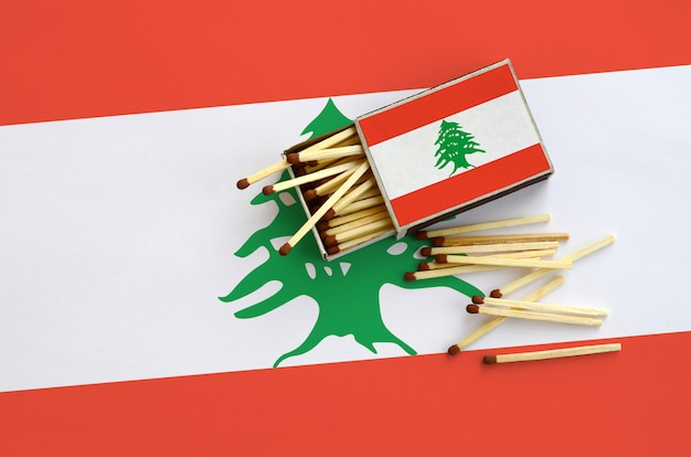Lebanon flag  is shown on an open matchbox, from which several matches fall and lies on a large flag Premium Photo