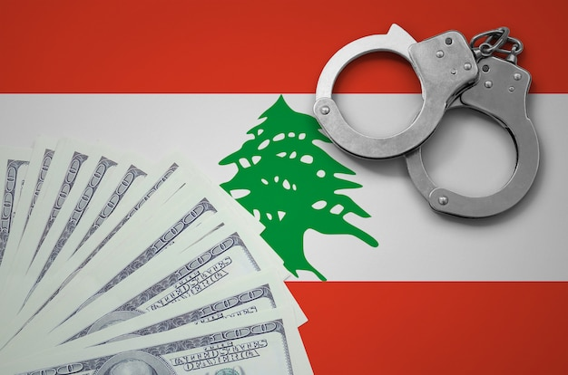 Lebanon flag  with handcuffs and a bundle of dollars. the concept of illegal banking operations in us currency Premium Photo