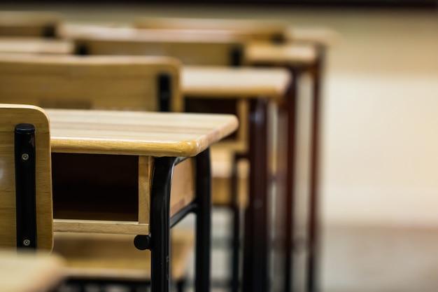 高校での授業を勉強するためのデスクチェアアイアンウッドのある講義室または学校の空の教室 Premium写真