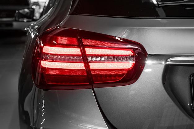 新しいハロゲングレークロスオーバー車のクローズアップテールライト。現代の車の外観。現代の車を照らすledの1つの詳細を閉じます。 Premium写真