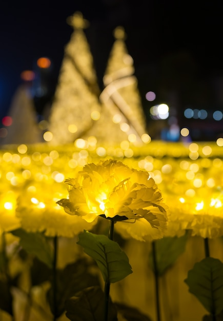 Led lights of yellow marigold fabric flower with gold christmas trees bokeh Premium Photo
