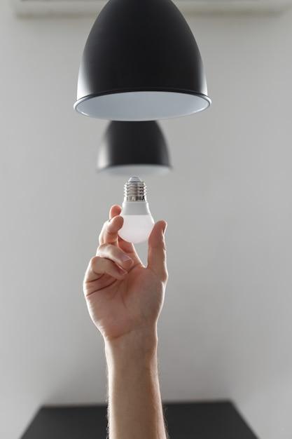 黒い色でフロアランプのled電球の電球を変更します。明るい灰色の背景に Premium写真
