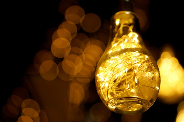夜の時間とぼやけて輝くライトのスイッチとビンテージ電球のクローズアップ装飾的なledライト。 Premium写真