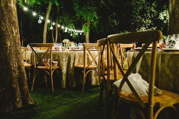 夜間の結婚式のための美しい装飾は、ledランタンで照らされ、そしてビンテージスタイルのセンターピース。 Premium写真