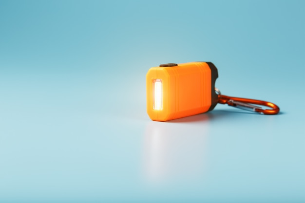 青色の背景にオレンジ色のled懐中電灯とカラビナが光っています。 Premium写真