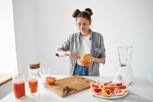 笑顔のグレープフルーツジュースやスムージーカットフルーツを作る女の子。健康的なlefestyleコンセプト 無料写真