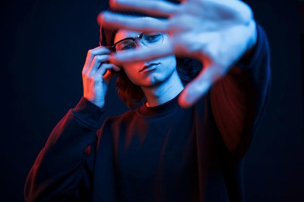 Левая рука размыта. студия снята в темной студии с неоновым светом. портрет серьезного мужчины Бесплатные Фотографии
