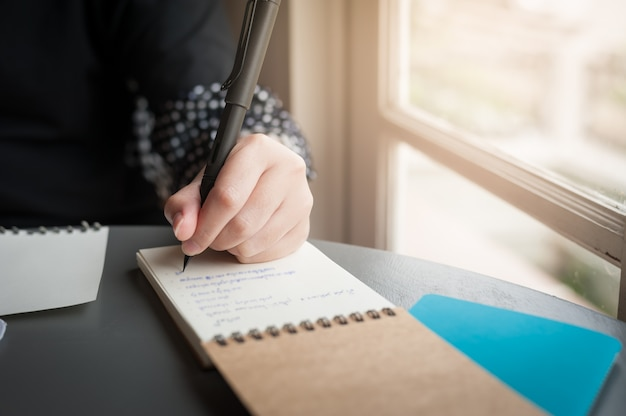 Left-handed woman with pen writing on notepad Premium Photo