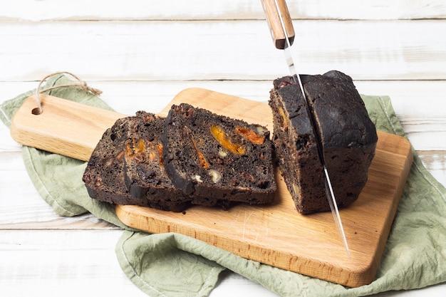 プルーン、アプリコット、クルミとデザートの黒パンの塊に左ナイフ。 Premium写真