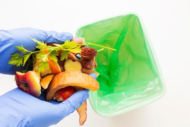 Avanzi di cibo sprecato e persona che indossa i guanti Foto Gratuite