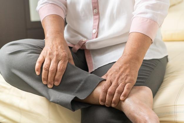 Старая женщина судороги ноги страдая от боли судороги ноги дома, проблема здравоохранения старшей концепции Premium Фотографии