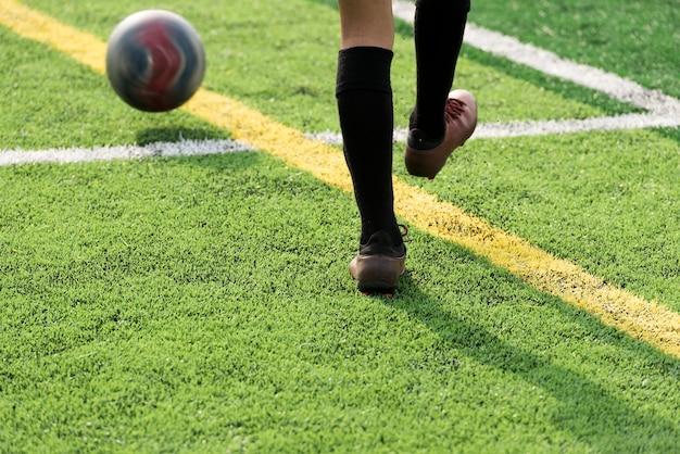 Leg of soccer player training in green soccer field Premium Photo