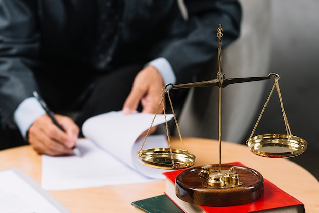 Legal adviser signing the contract with justice scale in foreground Free Photo