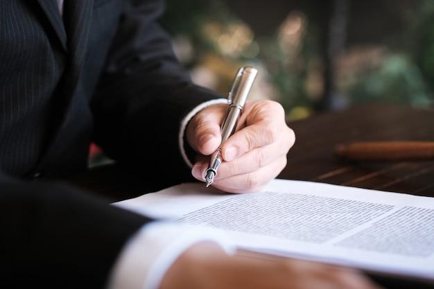 法律顧問は、小槌と法的法律との署名された契約をクライアントに提示します。正義と弁護士の概念。 Premium写真