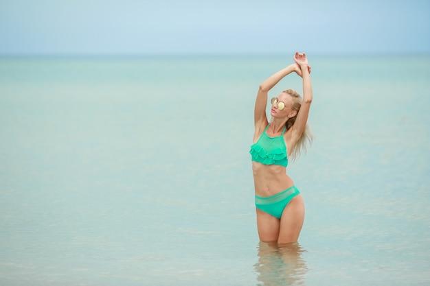 Веселая красотка позирует на берегу моря