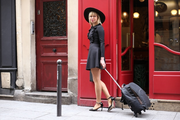 Длинноногая блондинка в коротком черном платье с шляпой и чемоданом идет по улице в париже Premium Фотографии