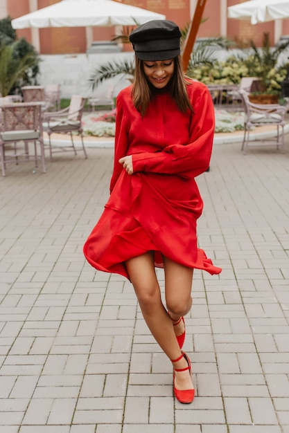 Длинноногая шатенка весело танцует на террасе ресторана. модель с отличным стилем развлекается для нового снимка Бесплатные Фотографии