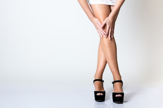Legs of  beautiful young woman posing with white screen Free Photo
