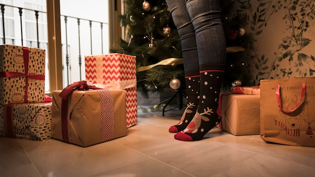 Legs in christmas socks between present boxes and decorated fir tree Free Photo