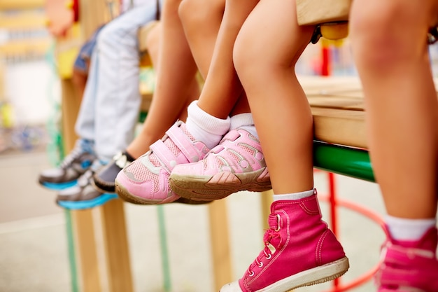 Legs of classmates sitting on the playground Free Photo