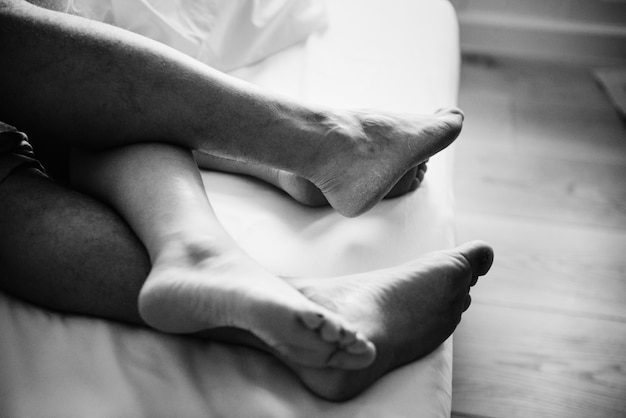 Legs of a couple sleeping in bed Free Photo