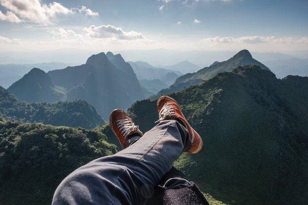Legs cross traveler relaxing and hanging on cliff with evergreen mountain Premium Photo