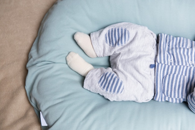 Legs and feet of baby lying on soft blue mattress Free Photo