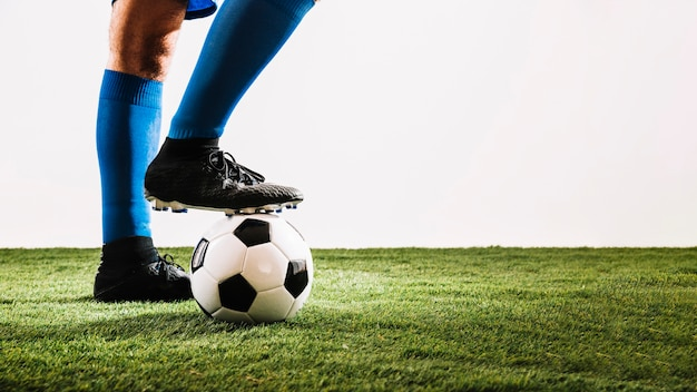 Legs in boots stepping on ball Free Photo