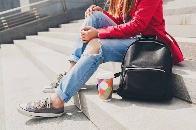 バックパックとコーヒーの大都市都会的なスタイルのトレンドが付いている通りにピンクのコートを着た若い流行に敏感な女性のスニーカーシューズトレンドの足 無料写真