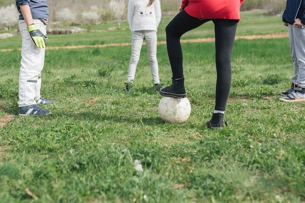 Legs of kids playing football Free Photo