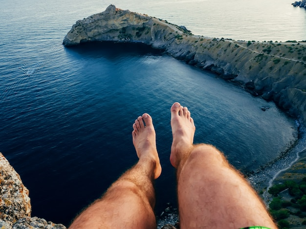 Legs of a man sitting on a mountain above the sea in the tourist camping Premium Photo