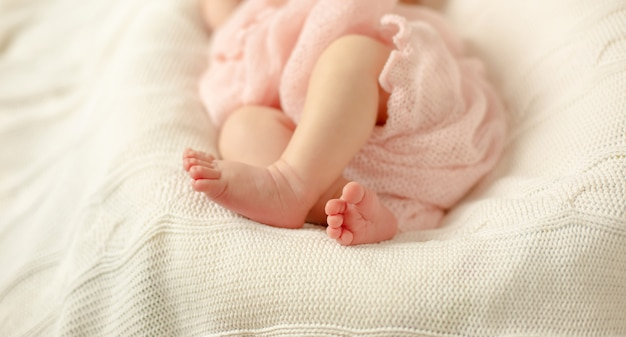 The legs of a newborn baby wrapped in a pink blanket lying on a white knitted blanket . selective focus. Premium Photo