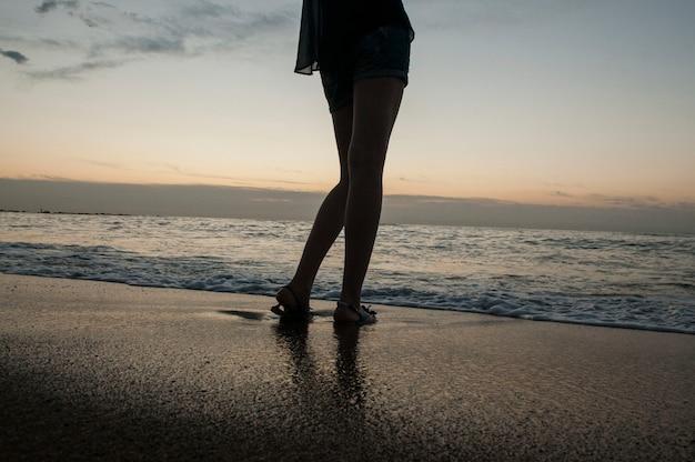 Ноги молодой девушки на море и песчаном пляже Premium Фотографии