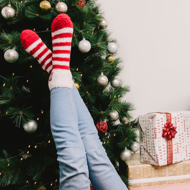 legs of woman in front of christmas tree free photo