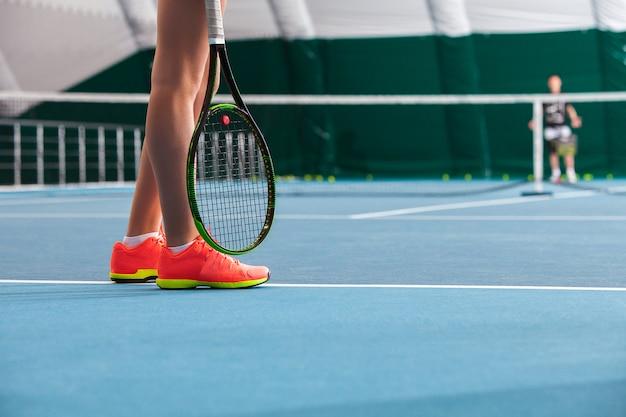 Ноги молодой девушки на закрытом теннисном корте с мячом и ракеткой Бесплатные Фотографии